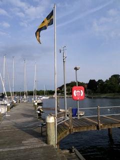 Die Stege sind mit Vereinswimpel gekennzeichnet. SVAOe gelbes Kreuz auf schwarzem Grund. Die Crew von Molly wechselt fast jede Woche. Jedes Crewmitglied soll sich sofort bekannt machen.