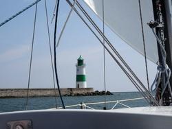 Auslaufen aus der Schlei. Die Mündung ist durch einen Leuchtturm in Grün und Weiß markiert. Er war früher (!) in Schwarz und Weiß gestreift.